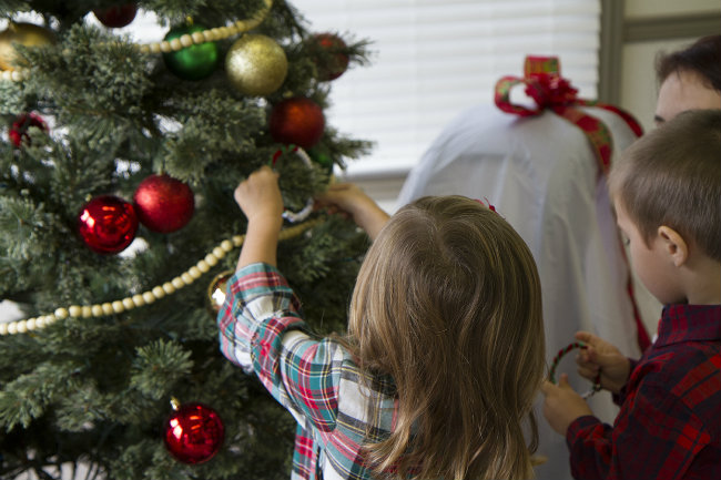 Toddlers hanging their homemade ornament on the tree